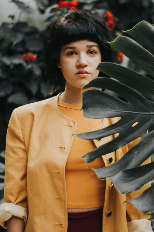 Woman Standing Behind Plant