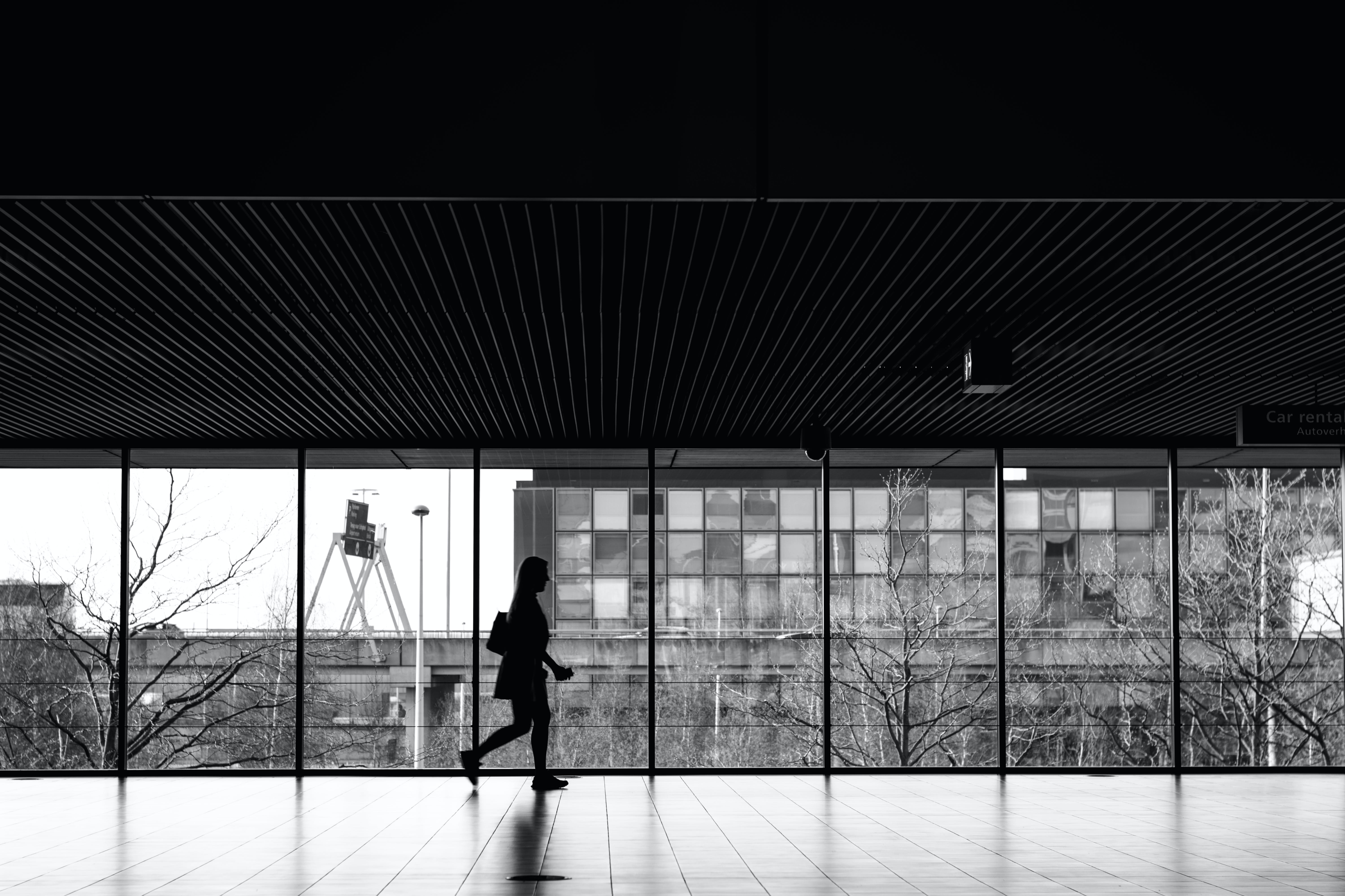 Free stock photo of airport, black and white, woman walking