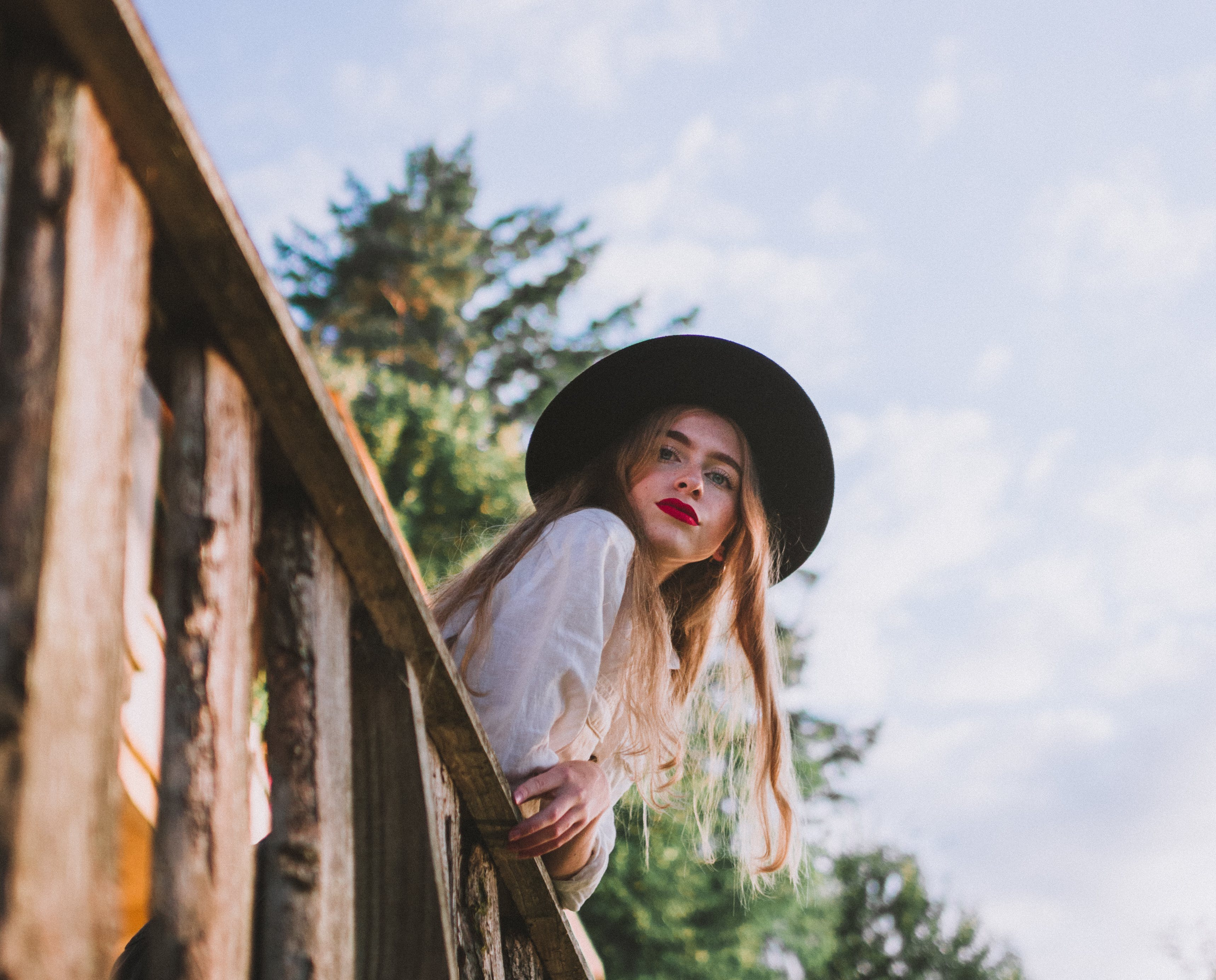 Woman Wearing Sun Hat Leaning on Wooden Railing