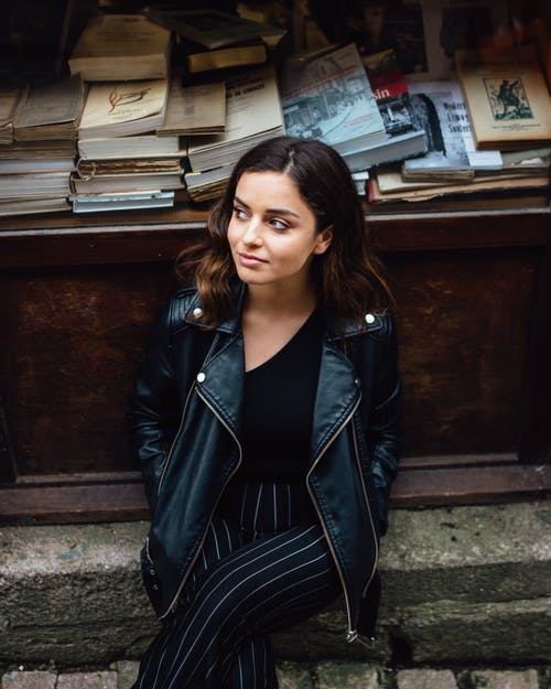 Photo of Woman in Black Leather Jacket Sitting on Stone Curb In Front of a Wooden Table with Books Posing while Looking Away