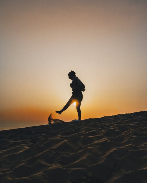Silhouette of Woman Kicking Sand