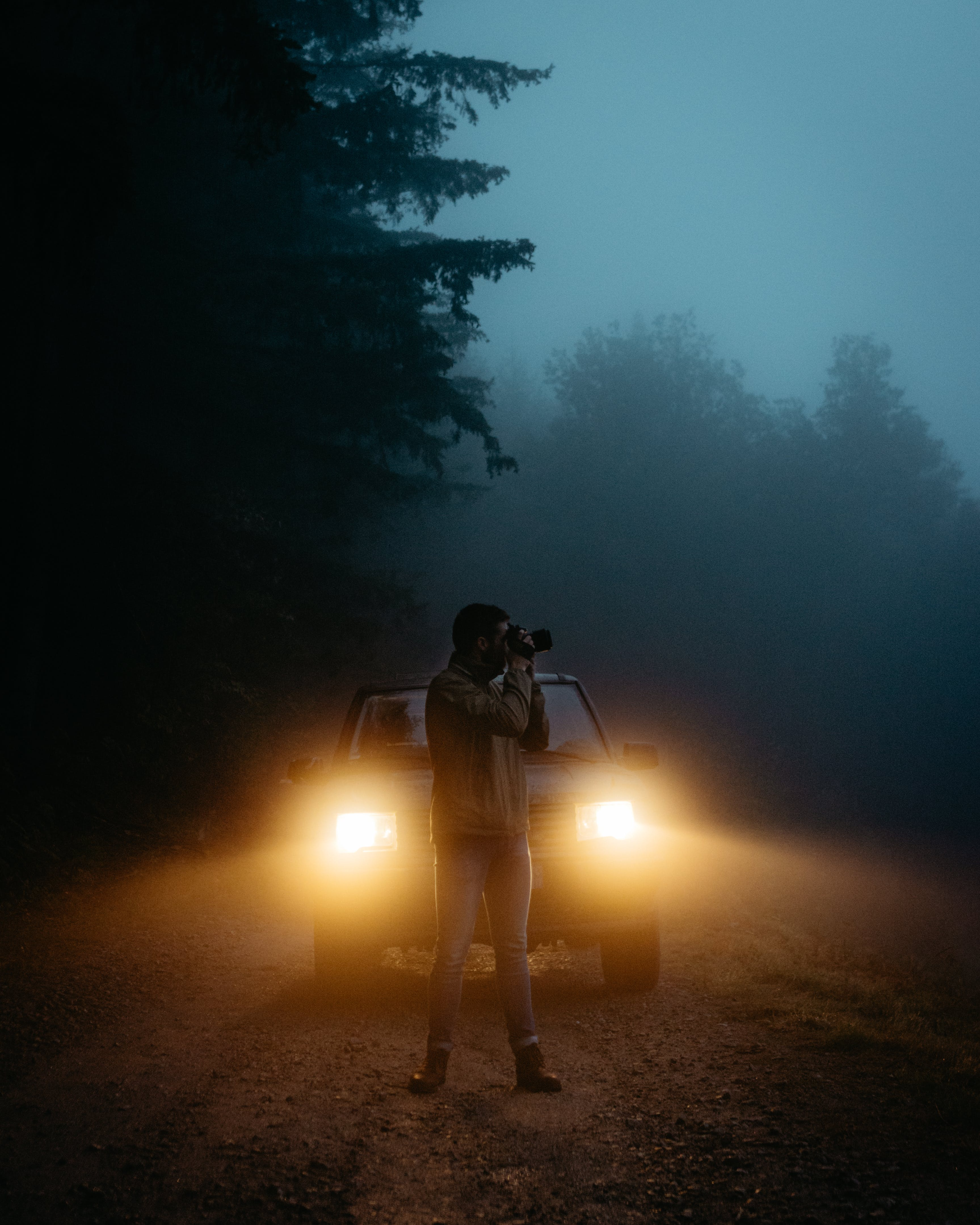 Man Taking Photo in Front of Vehicle