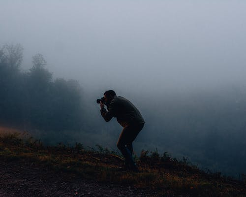Man Using Dslr Camera on a Foggy day