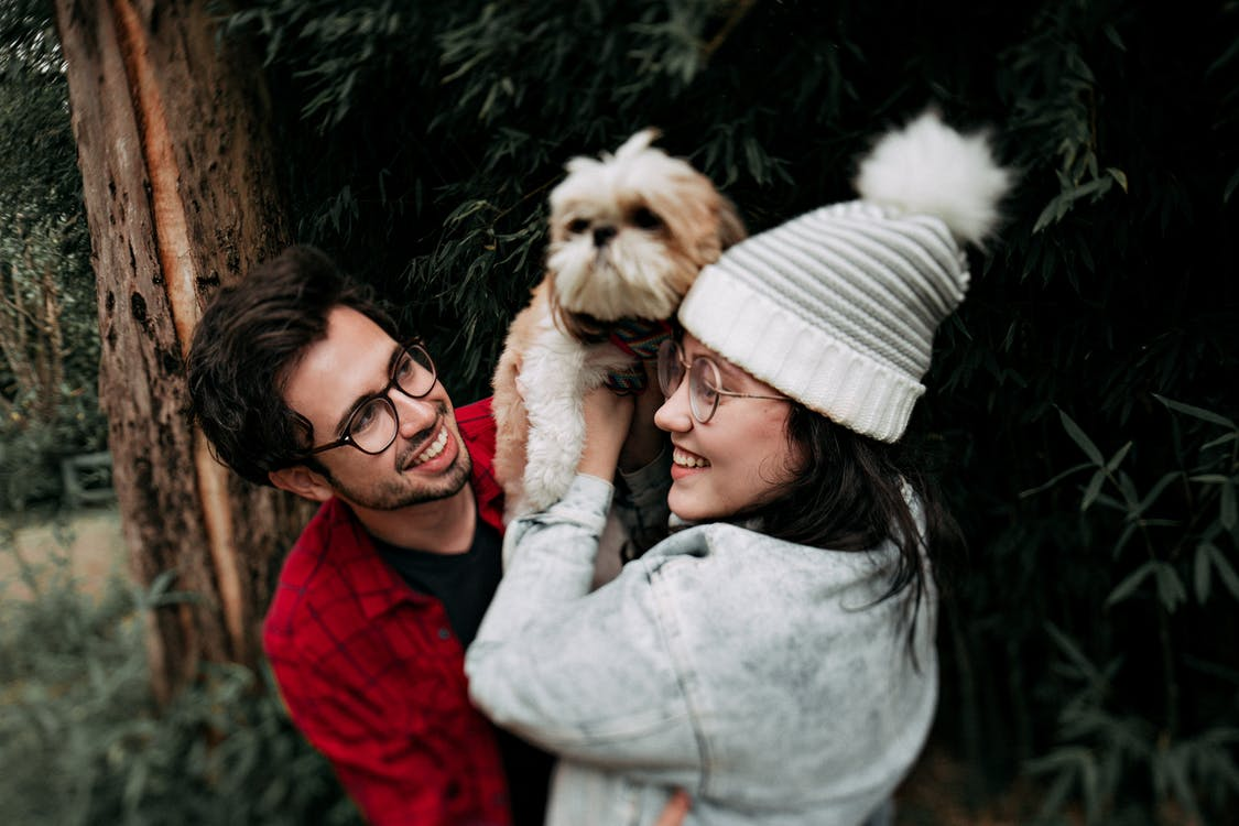 Woman Lifting Puppy in Front of Man Near Tree