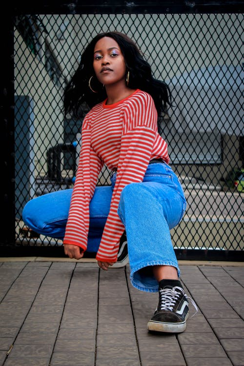 Photo of Woman in Red and White Striped Long-sleeved Shirt and Blue Jeans Squat Posing
