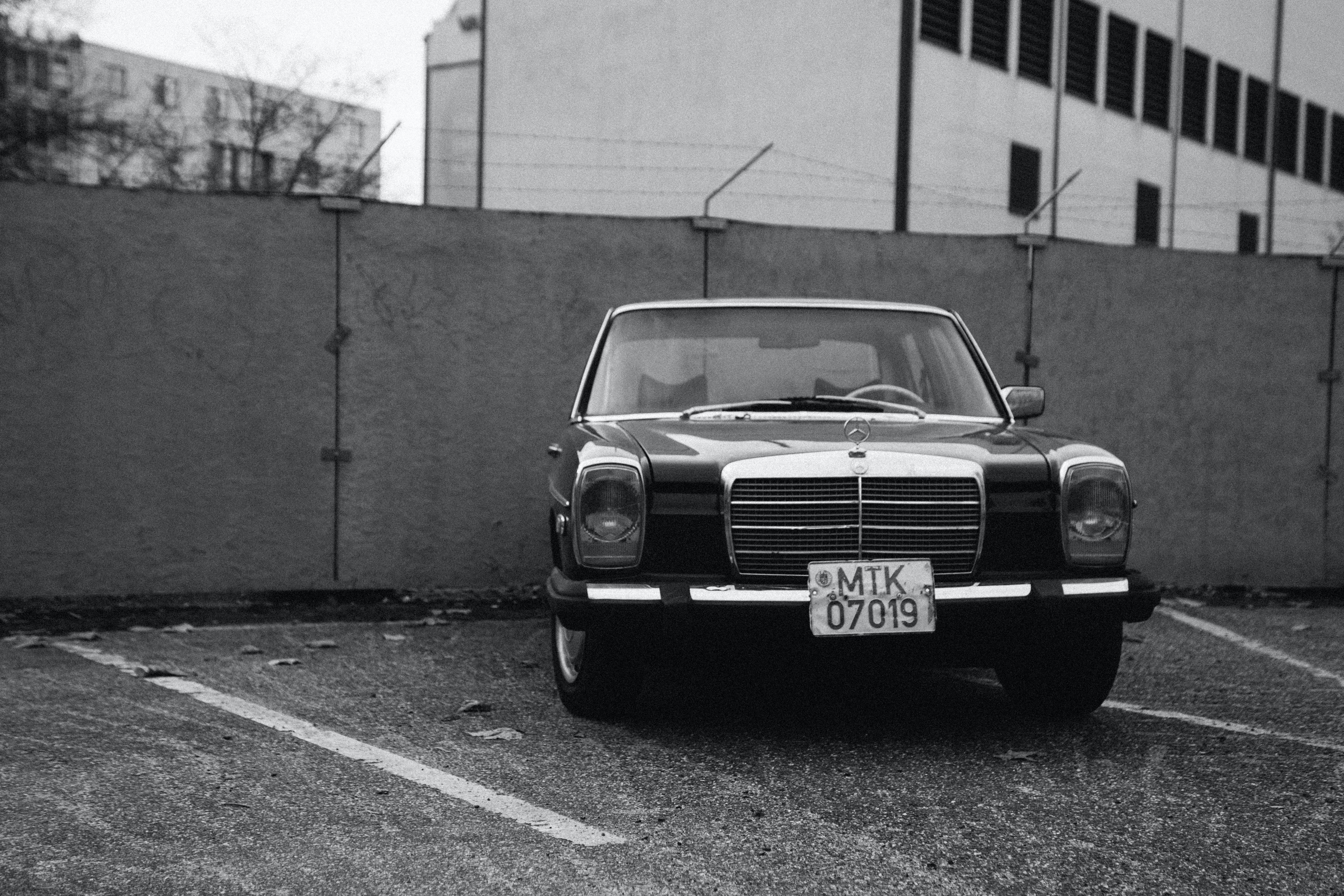 Black Vehicle Parked Near Concrete Wall in Grayscale Photography