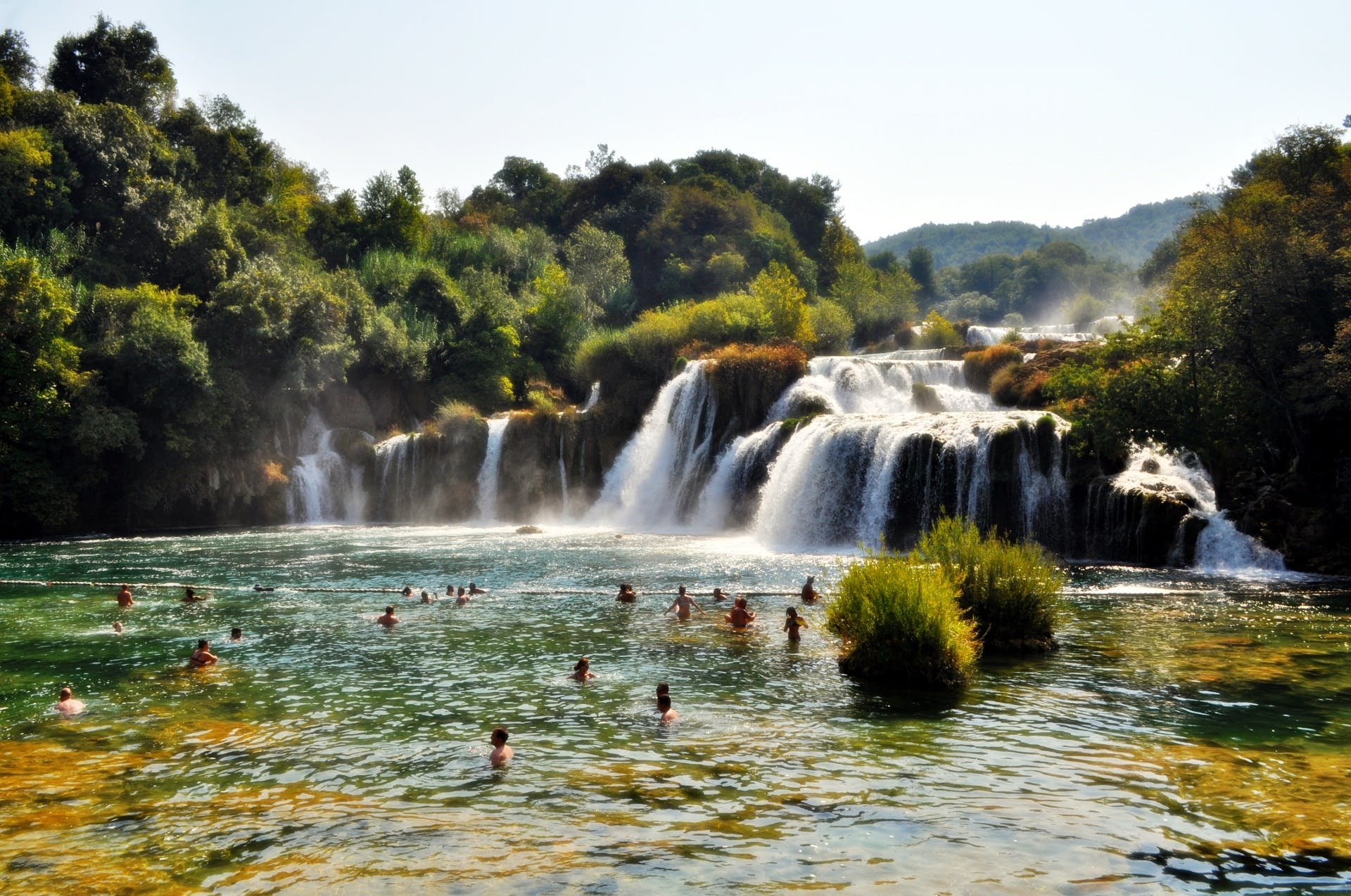 People Swimming Near Waterfall during Daytime