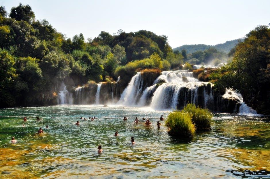 People Swimming Near Waterfall during Daytime · Free Stock