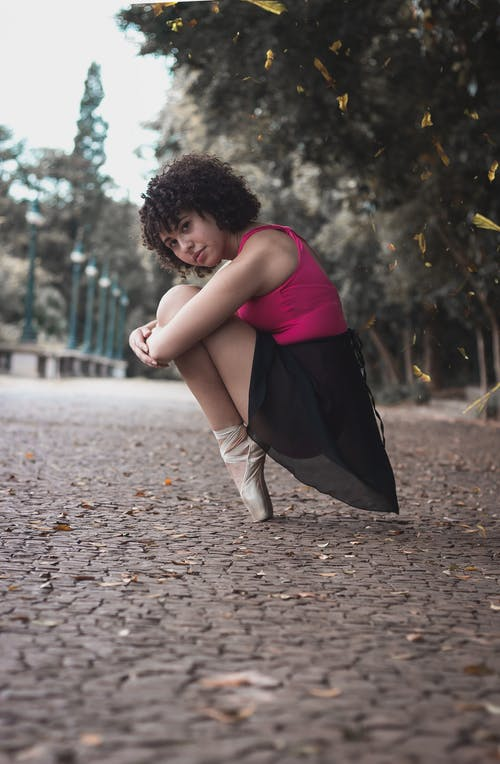 Sitting Ballerina Beside Green and Brown Trees
