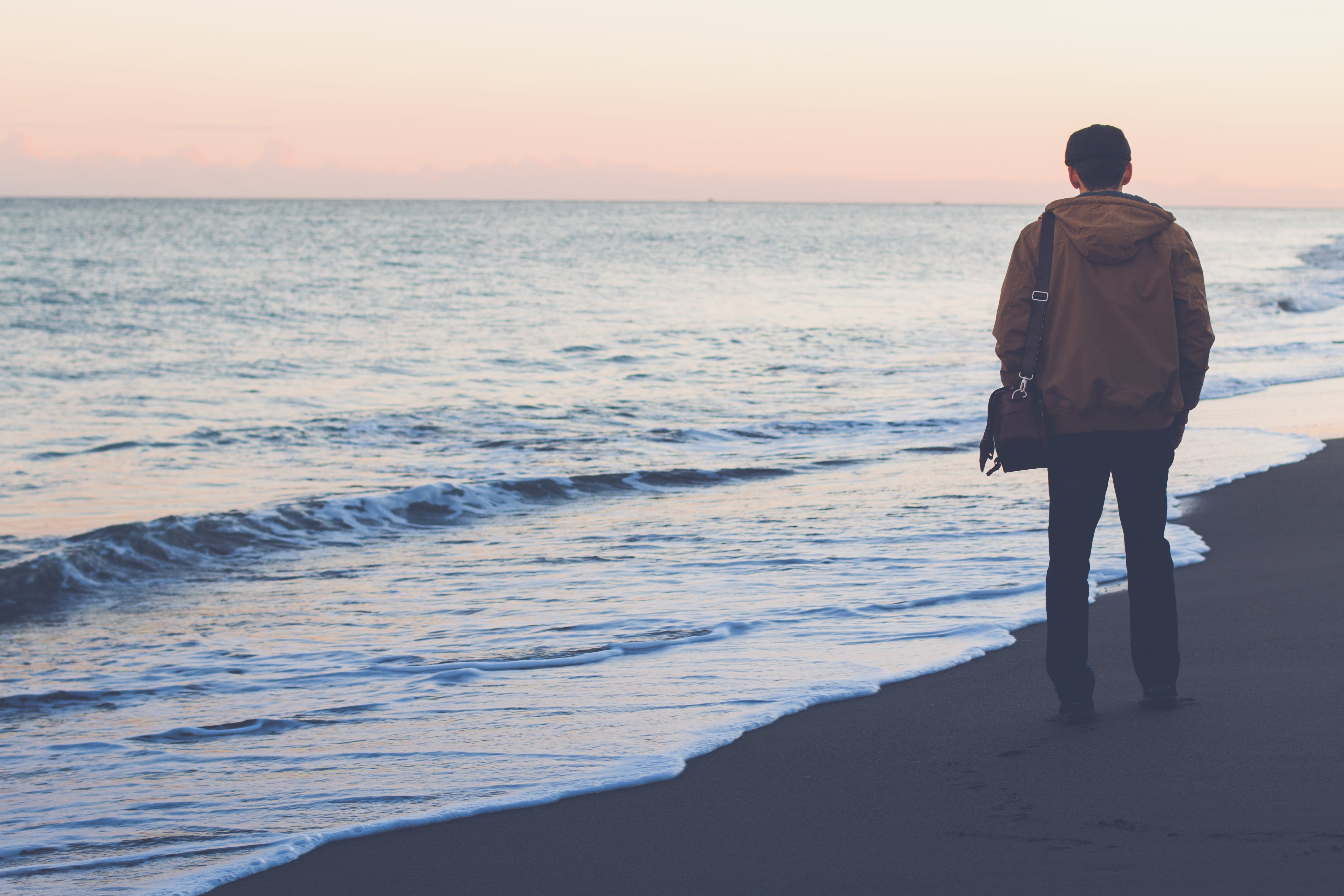 Man Standing on Seashore While Carrying Bag