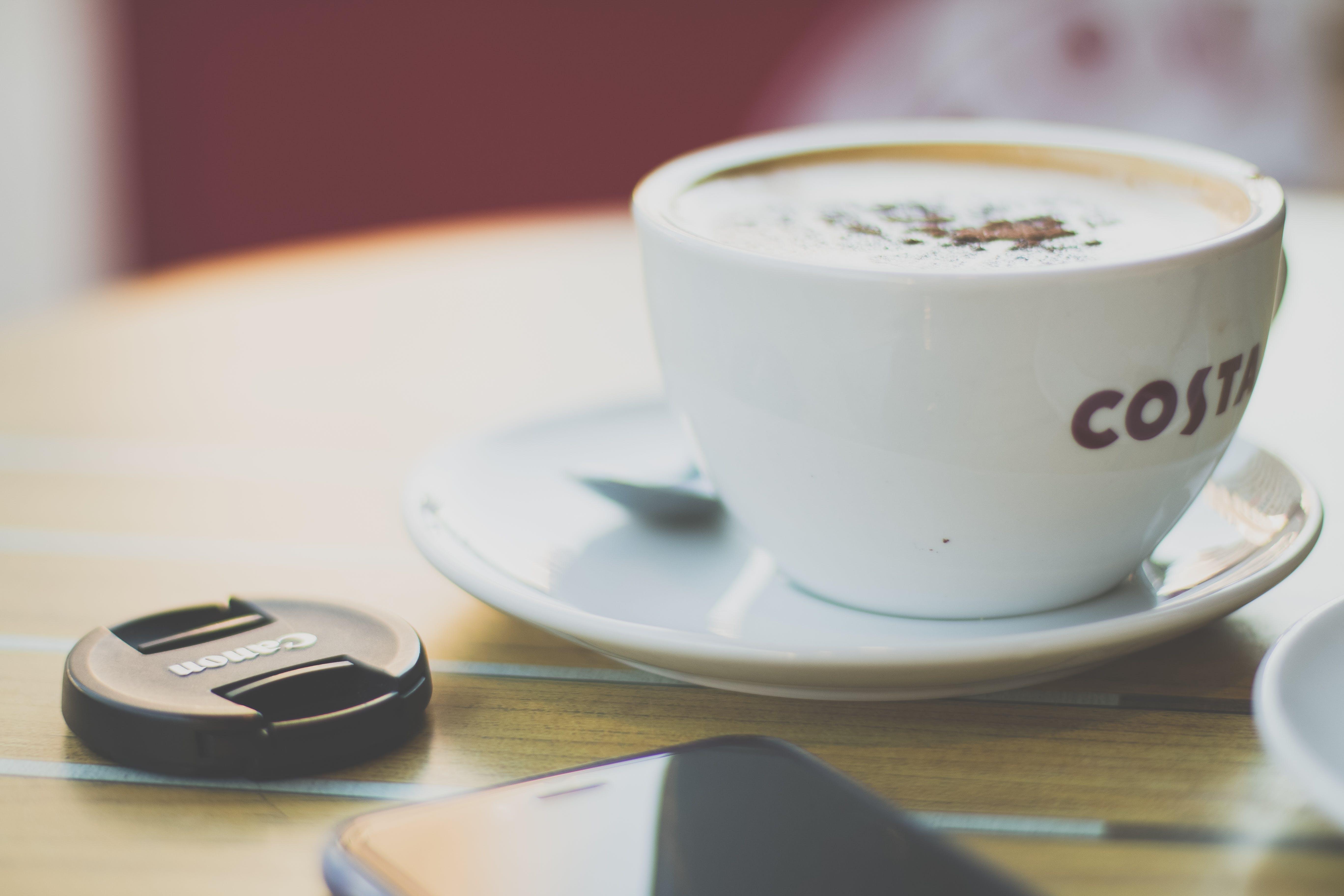 White Ceramic Cup Beside Black Smartphone