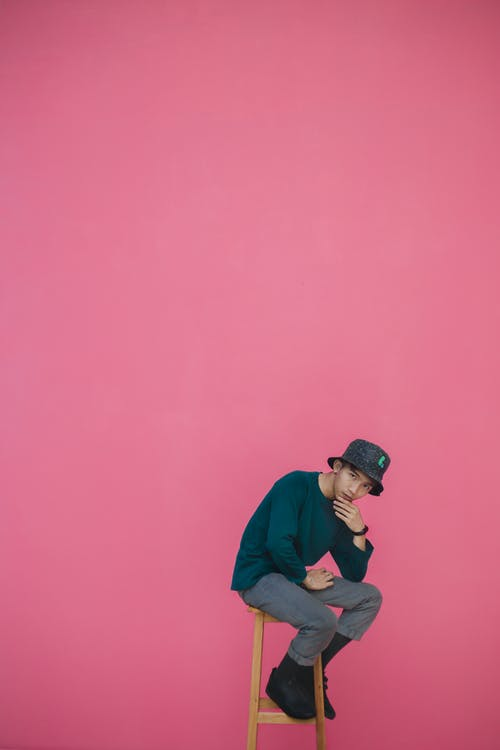 Man Sitting on Wooden Stool Against Pink Background