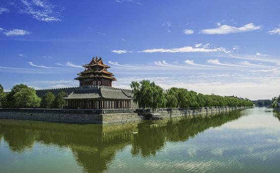 Concrete Temple Near Body of Water Under Blue Sunny Sky