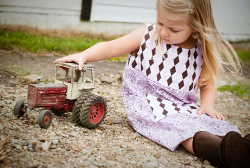 Girl Sitting on Brown Sand While Playing Tractor Toy