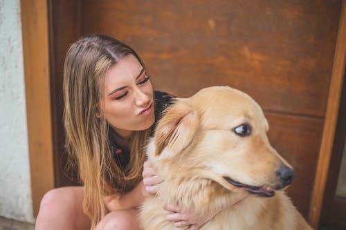 Woman Hugging Tan Dog
