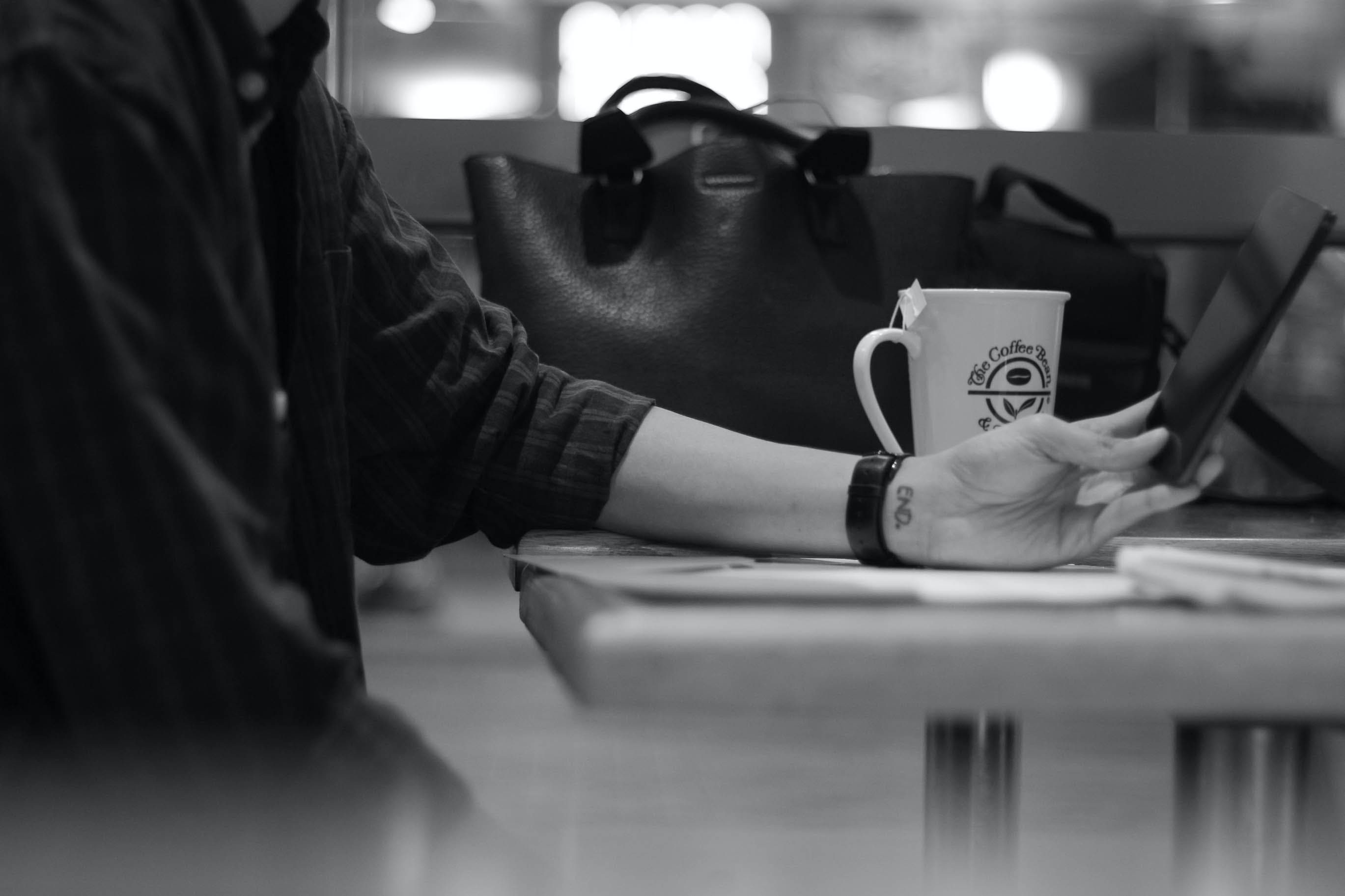 Gray Scale Photograph of Person Sitting Beside Black Leather Bag