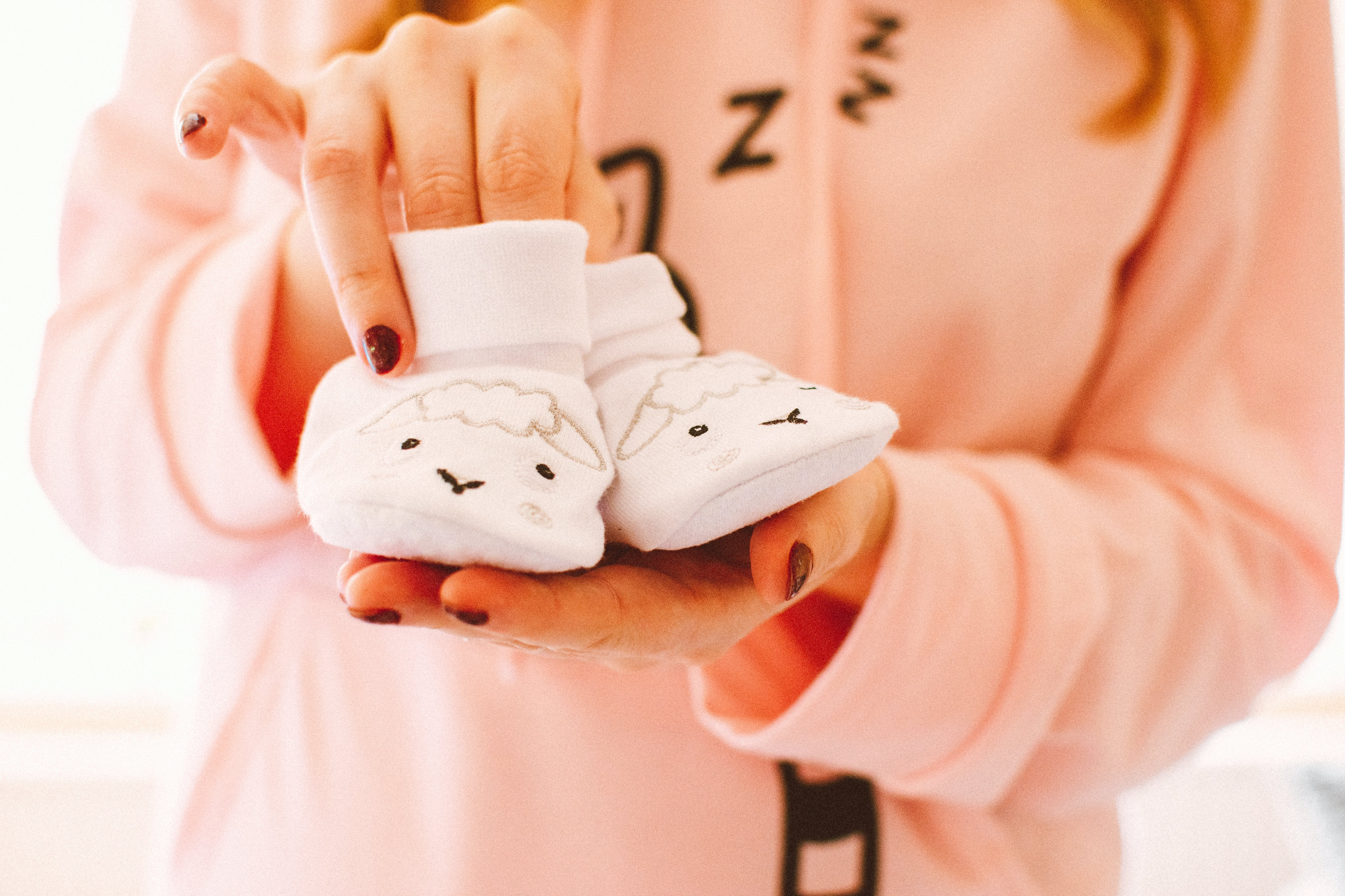 Woman Holding Baby's Pair of White Shoes