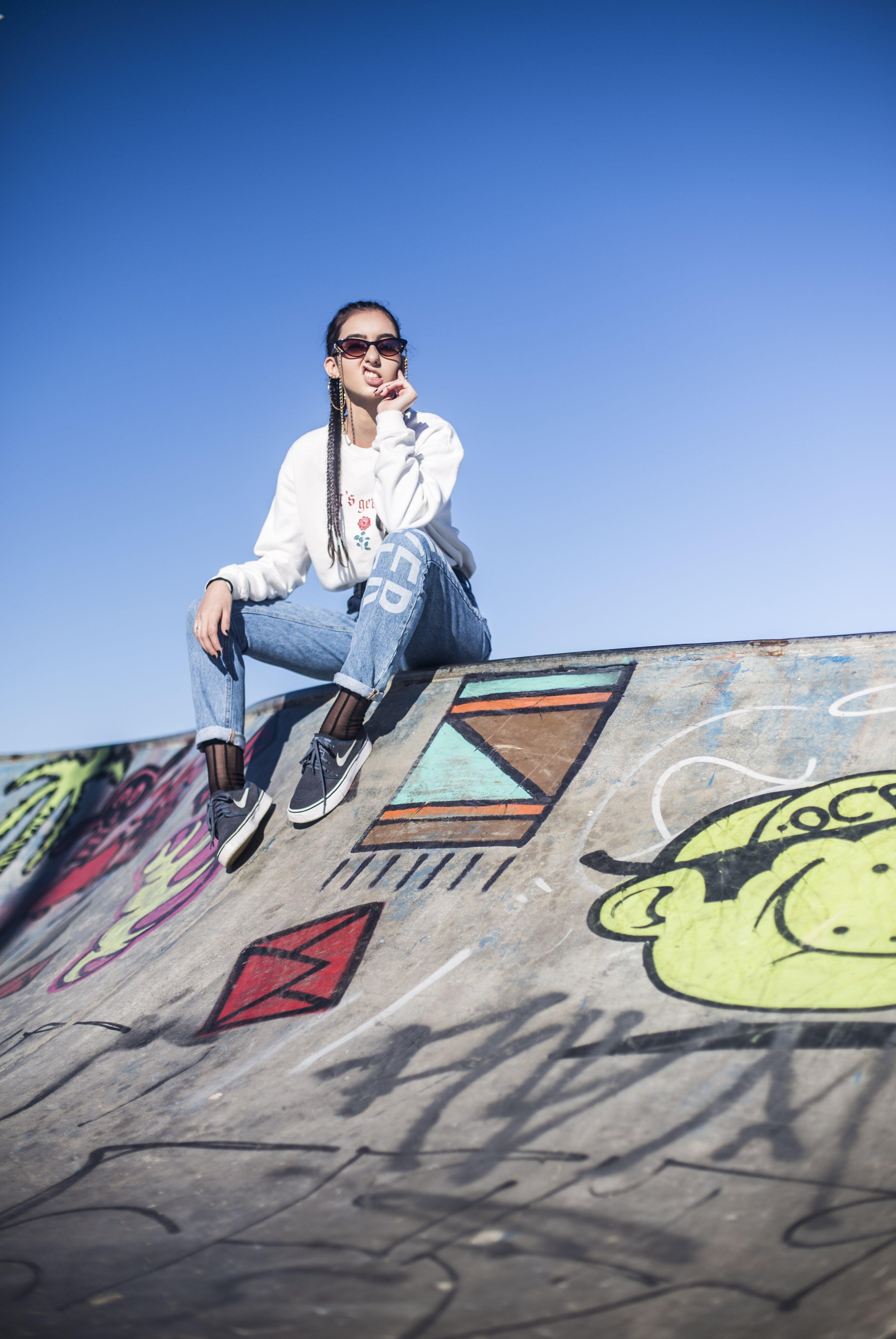 Woman Sitting on Graffiti Painted Skate Park