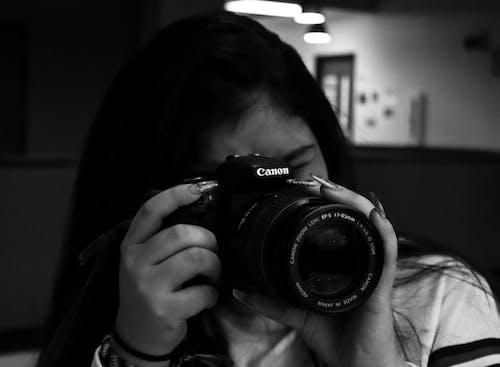 Foto d'estoc gratuïta de blanc i negre, càmera, càmera que sosté la persona, DSLR