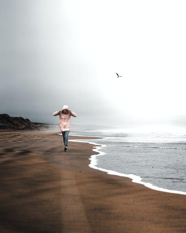 Person Walking Near Shore
