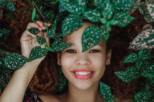 Photo of Woman Smiling Near Leaves