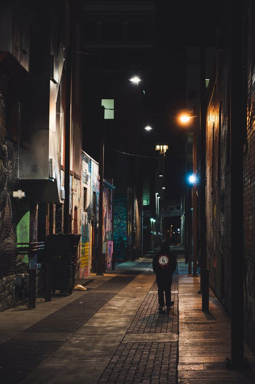 Person Walking On Alley At Nighttime