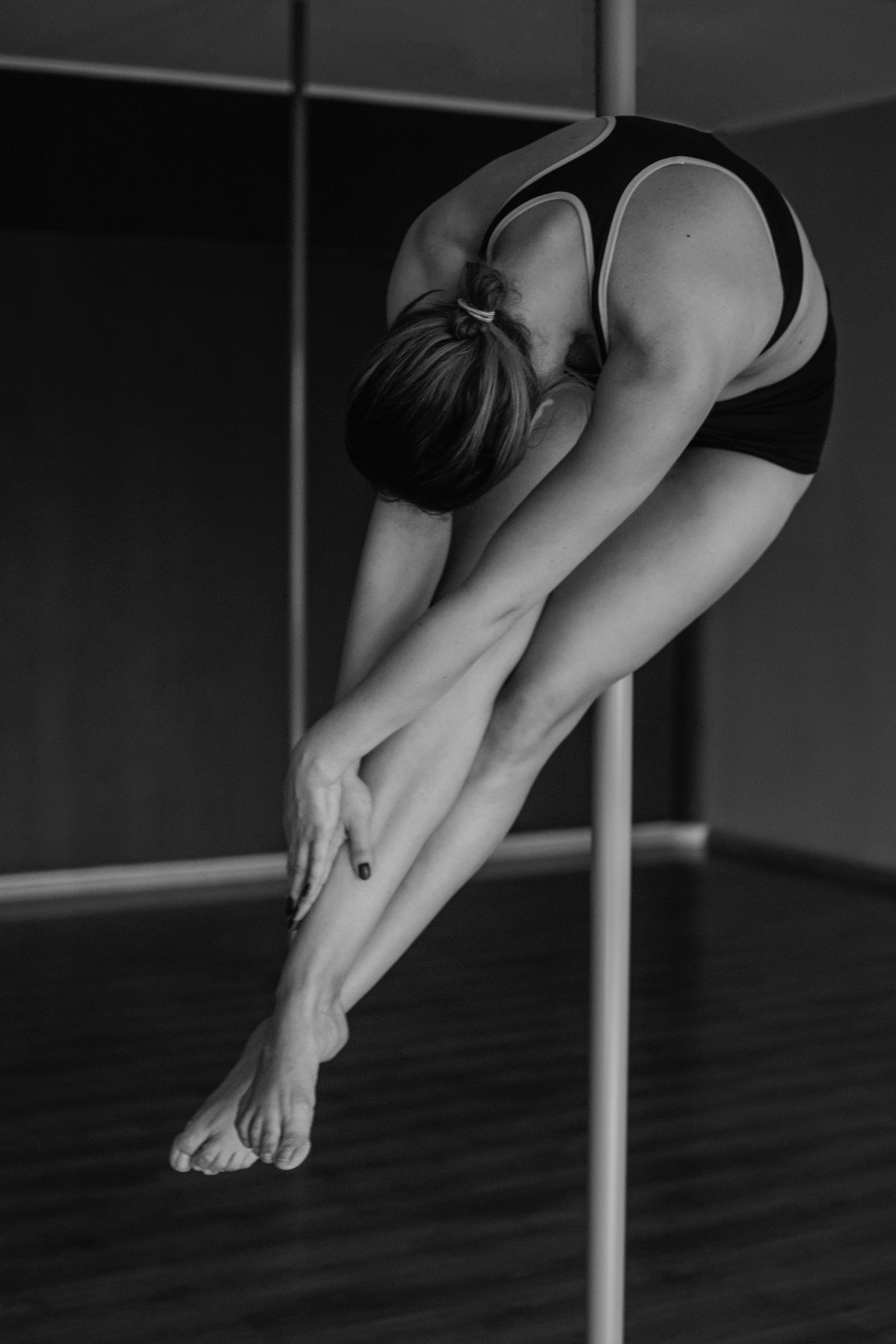 Grayscale Photography of Woman on Pole