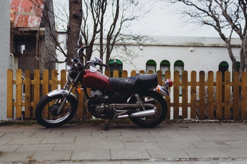 Black and Maroon Motorcycle Parked Beside Brown Wooden Fence