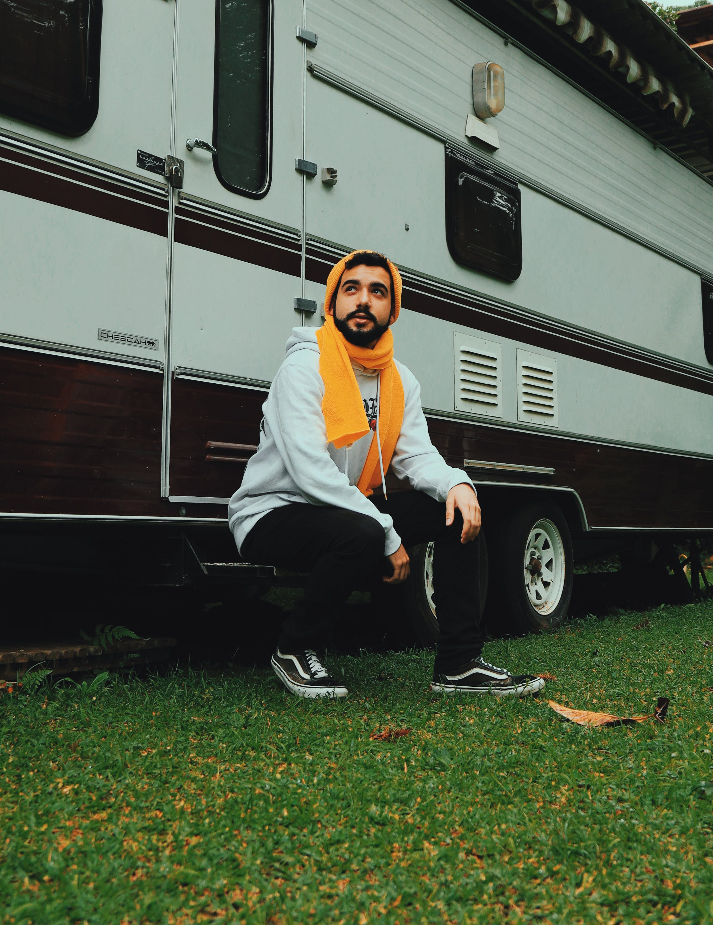 Man Sitting on White and Brown Recreational Vehicle