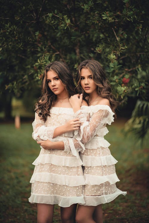 Two Standing Women Wearing White Off-shoulder Dresses Near Green Trees