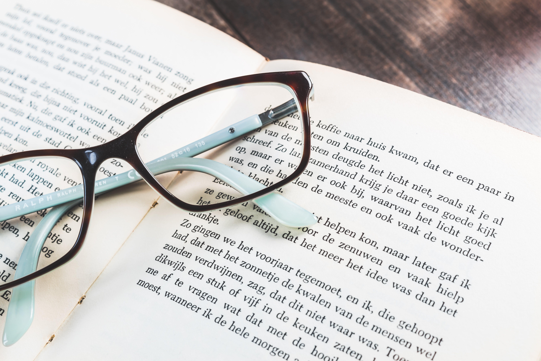 Black Framed Eyeglasses On Open Book