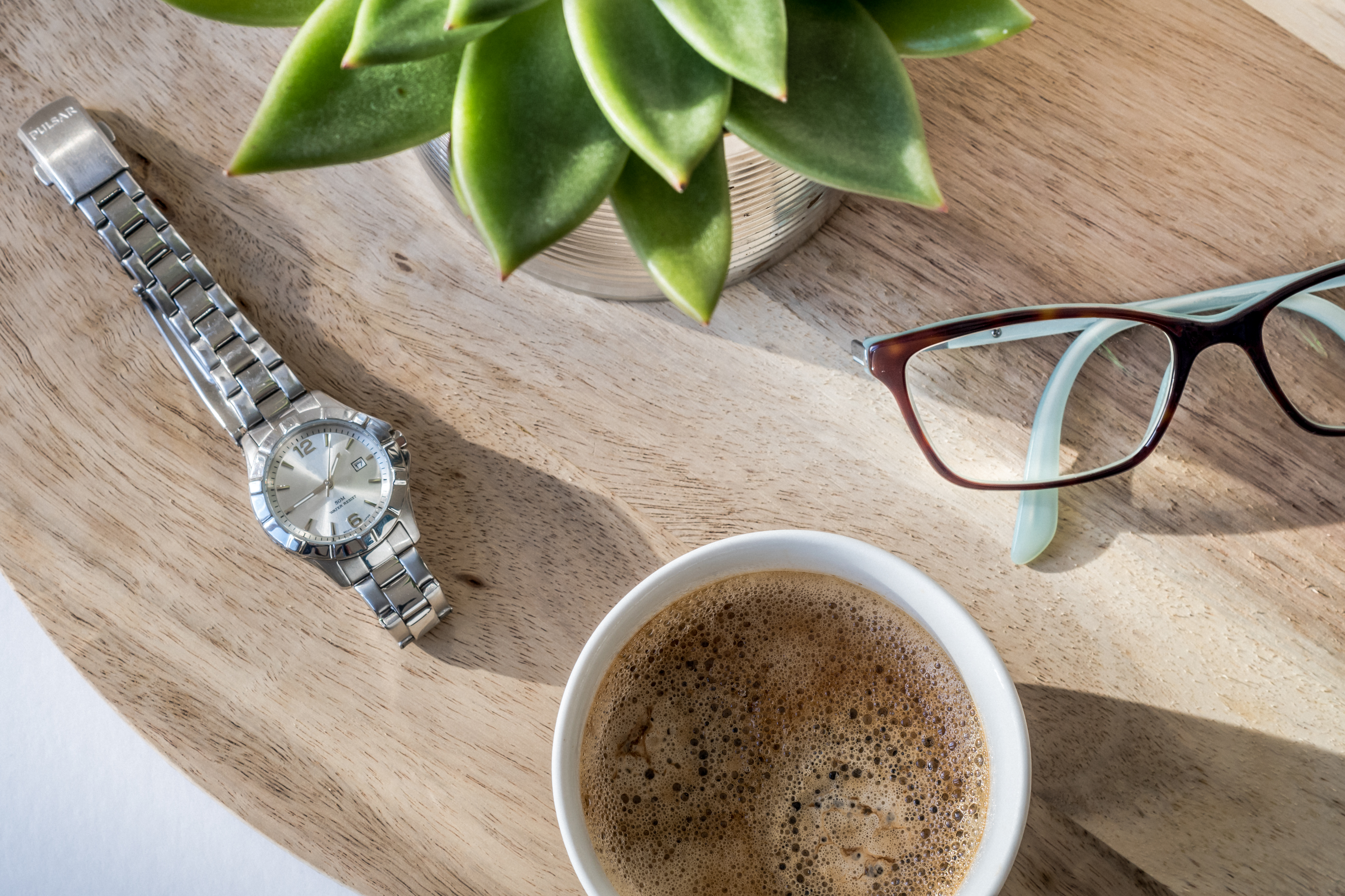 A Cup Of Coffee, Stainless Watch And Eyeglasses On A Table With Ornamental Plant