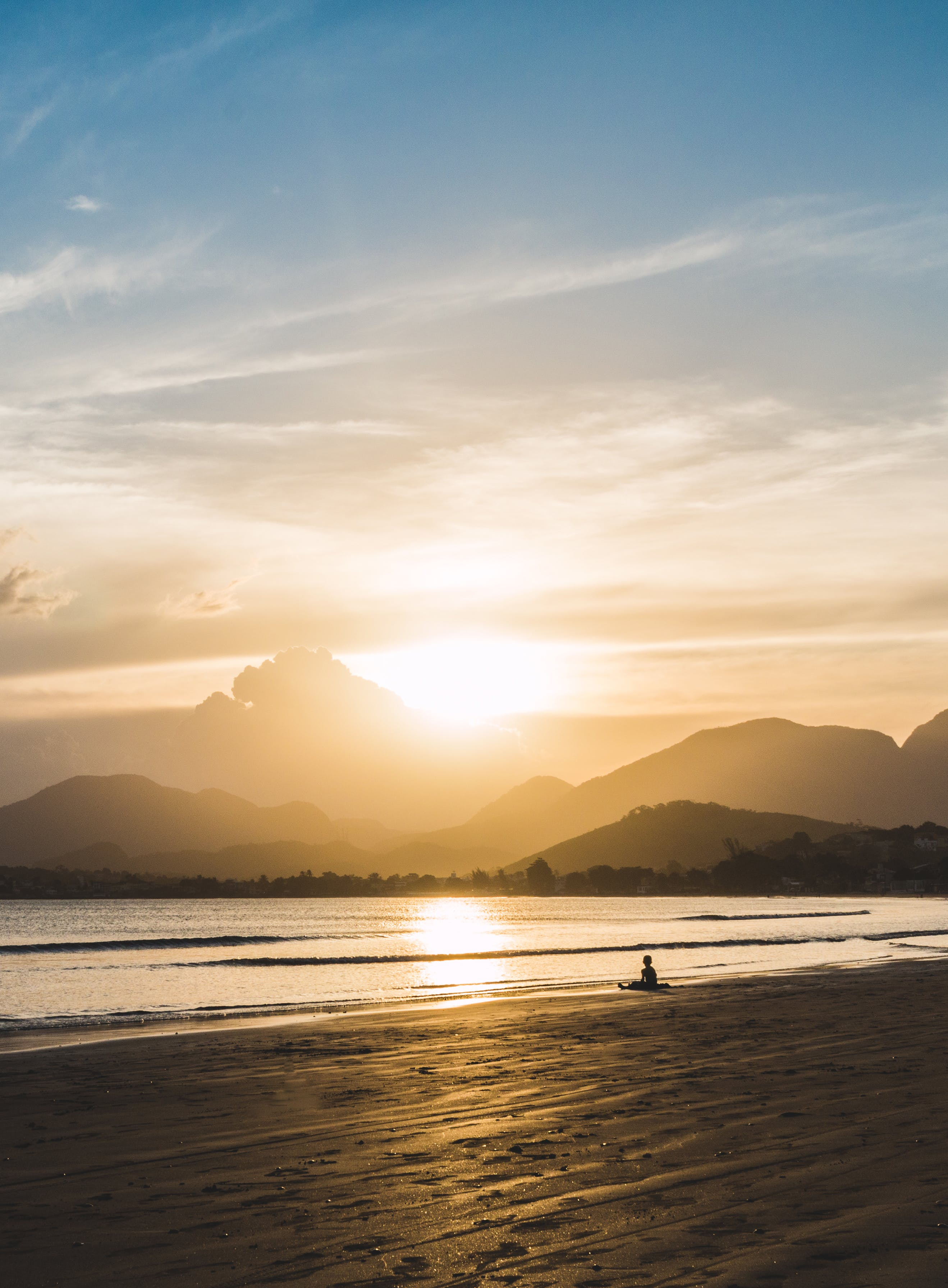 Person Sitting on Beach during Golden Hour