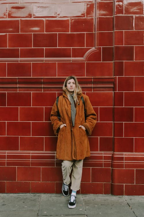 Woman Leaning on Red Ceramic Wall