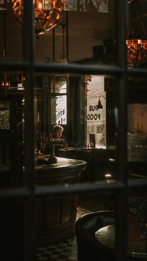 A Lone Person Seated On A Table Of A Cozy Old Pub