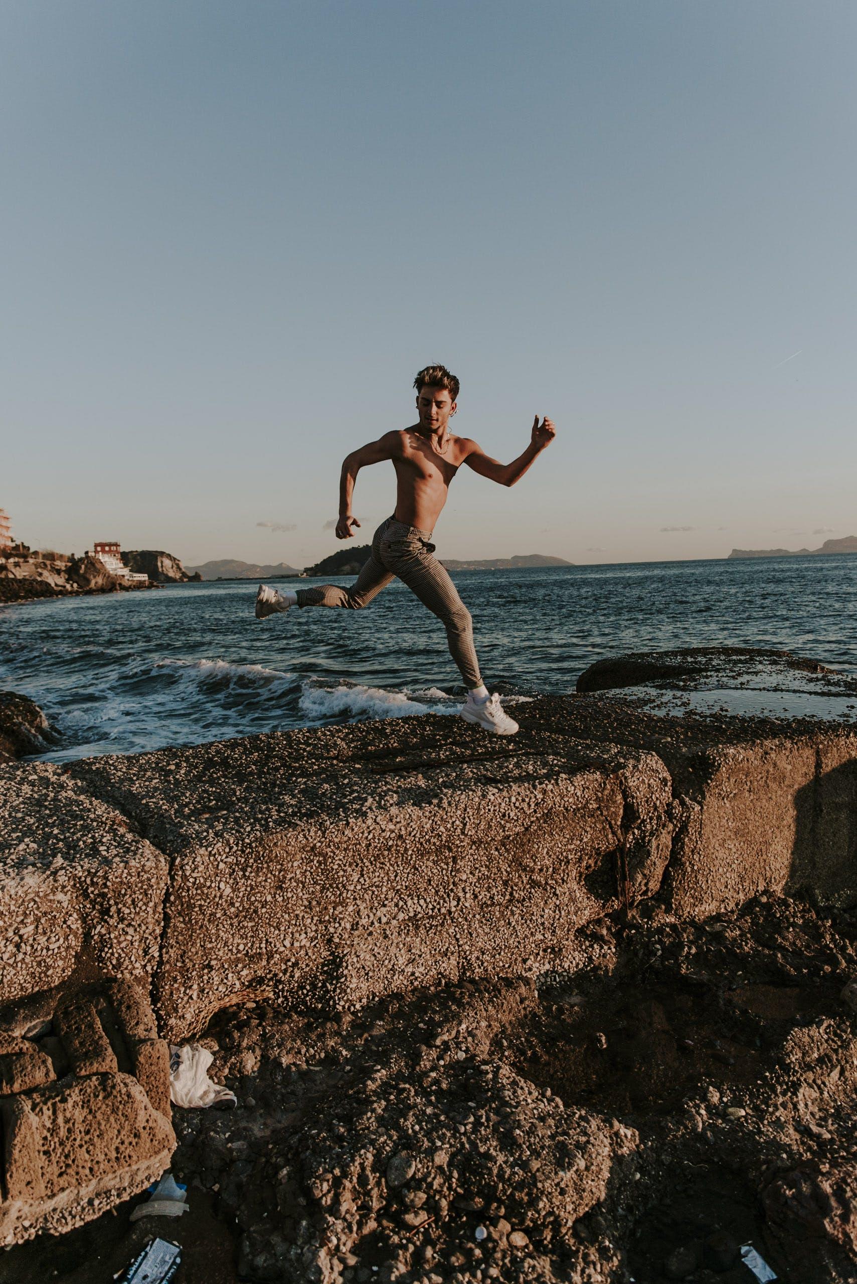 Man Jumping over Brown Barricade Near Shore