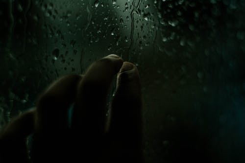 Person Touching Window With Dripping Water