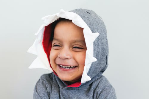 Boy Smiling Wearing Grey And White Hooded Top