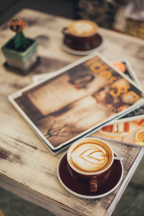 Two Lattes and Magazine on Brown Tray