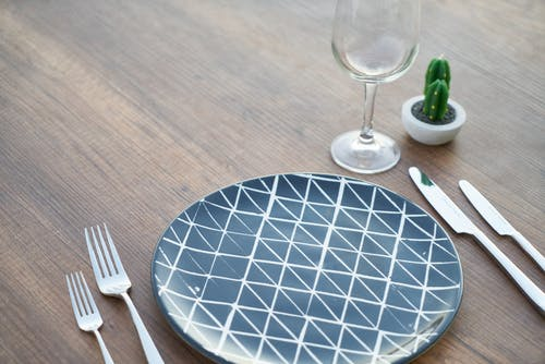 Round Blue and White Ceramic Plate, Two Forks, Two Knives, and Wine Glass