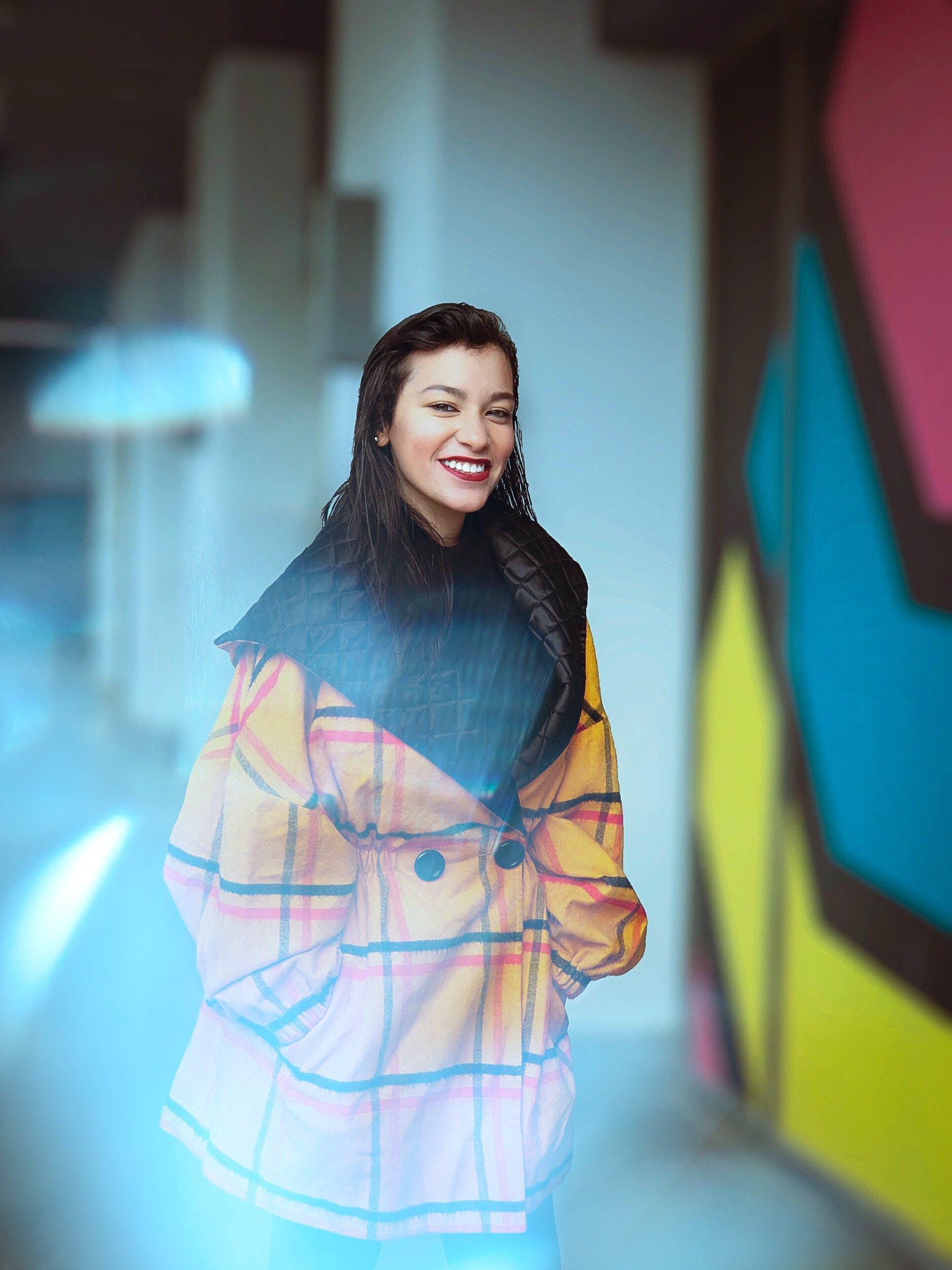 Woman Wearing Yellow Coat Smiling Near Wall