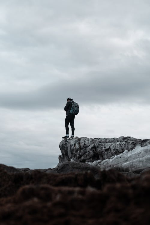 Man With Backpack Standing on Gray Cliff