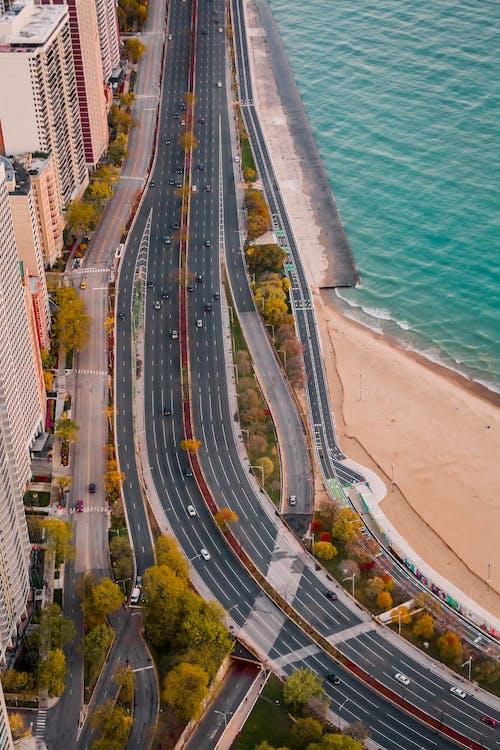 arabalar, binalar, çevre yolu, deniz kıyısı içeren Ücretsiz stok fotoğraf