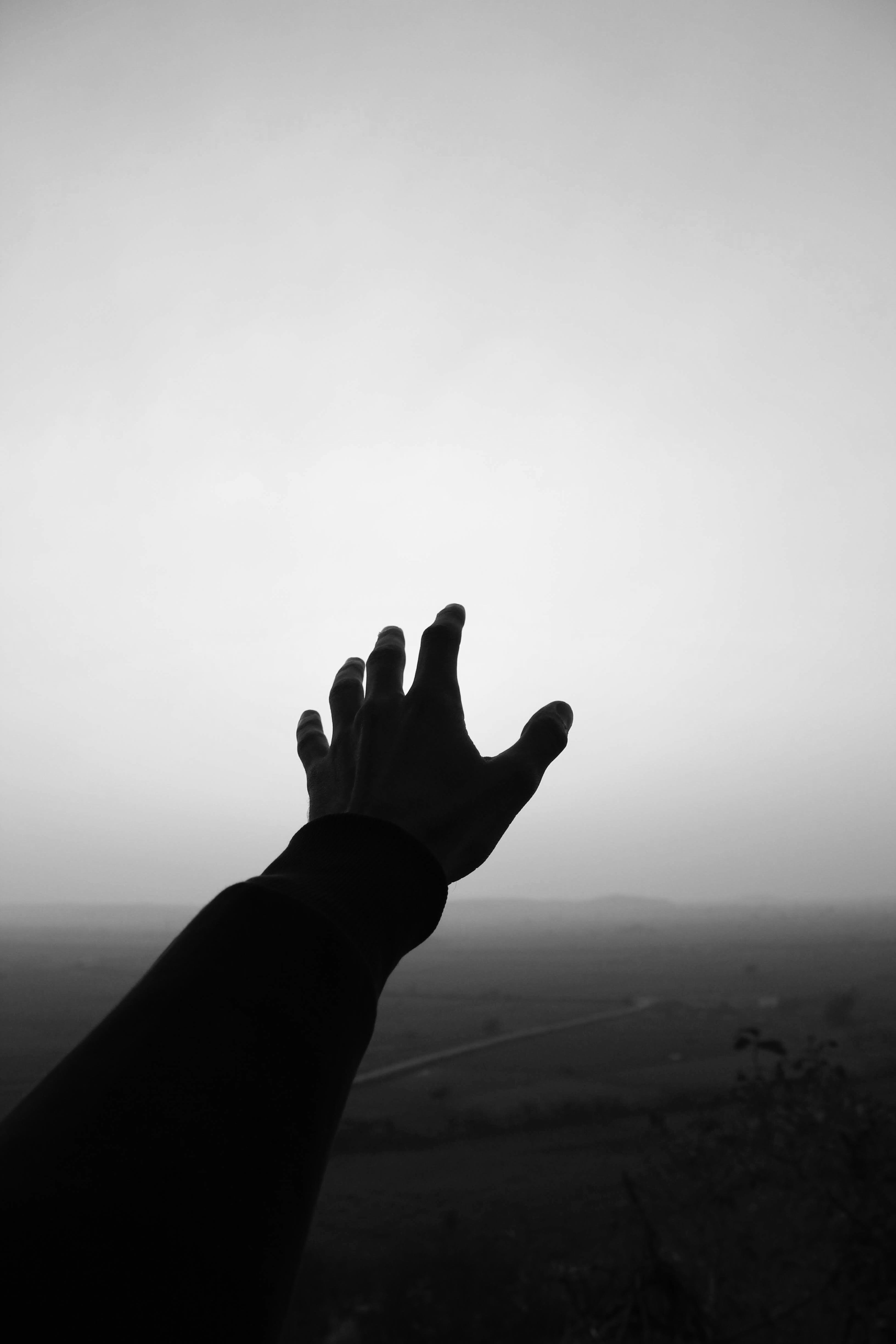 Grayscale Photo of Person's Hand Reaching For the Sky