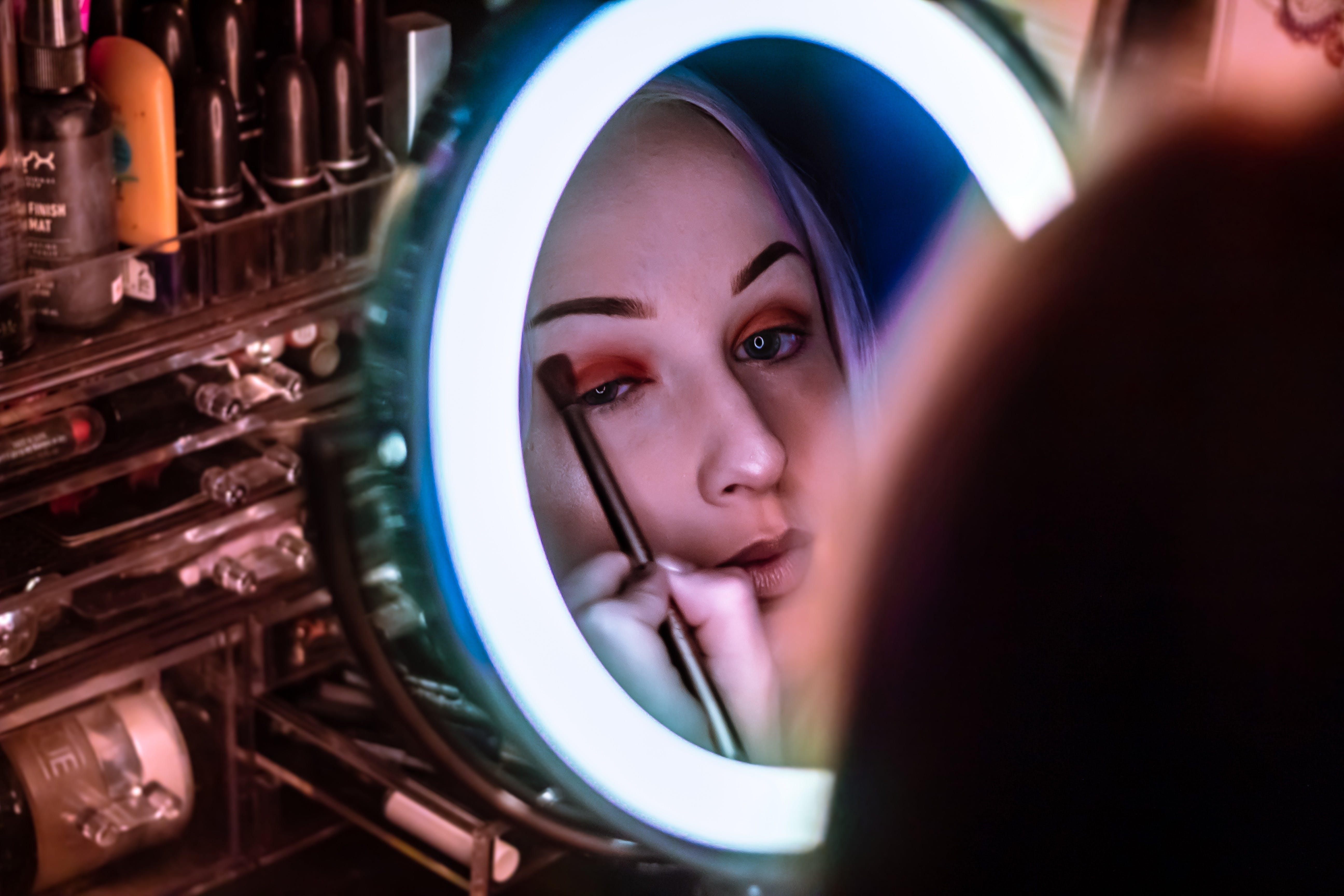 Woman Facing Mirror Applying Eyeshadow