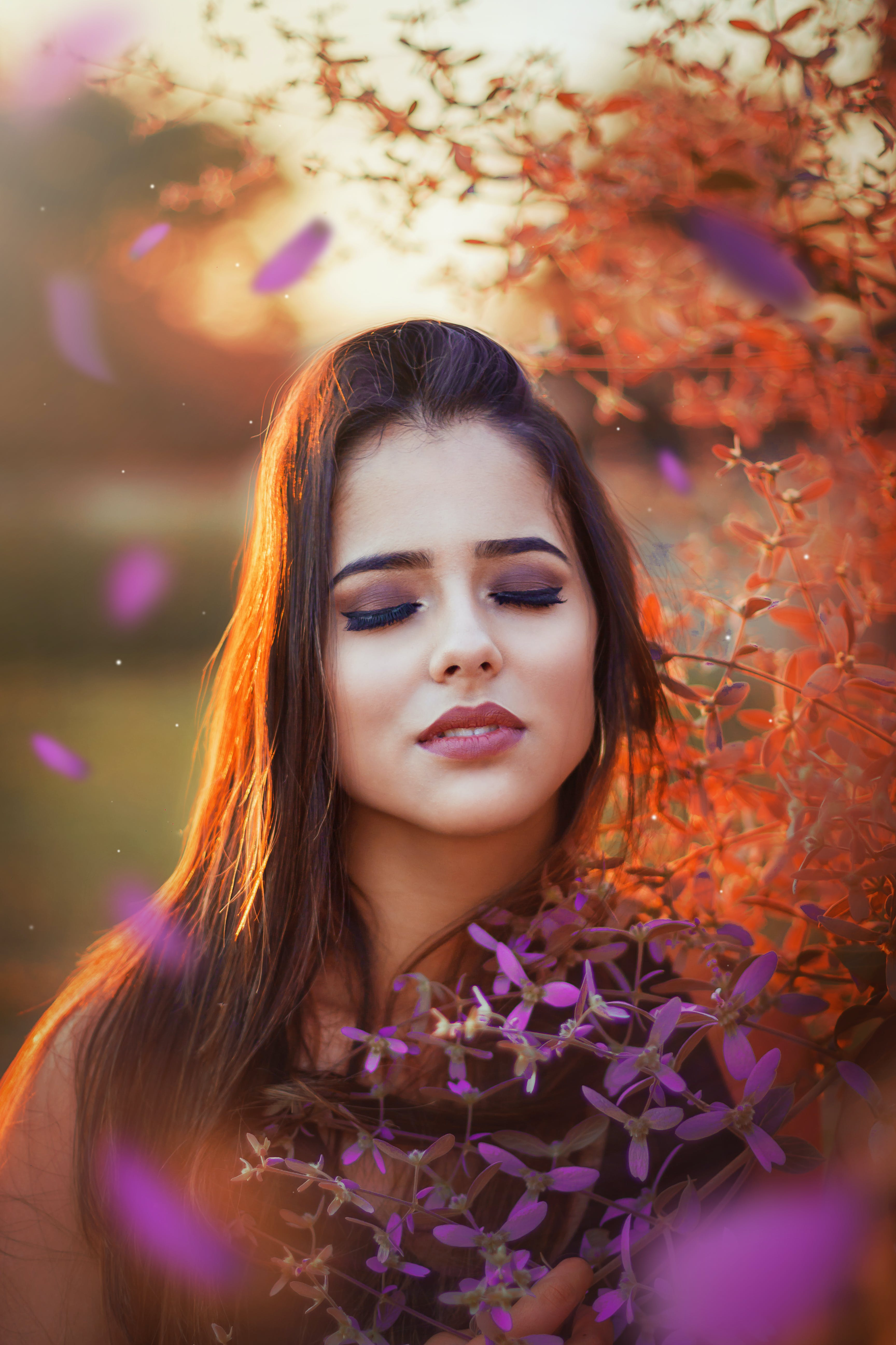 Photo of Woman With Her Eyes Closed Standing Beside Flowers