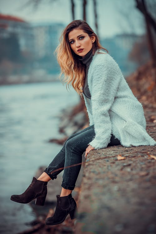 Photo of Woman in White Sweater Sitting on Concrete Riverbank