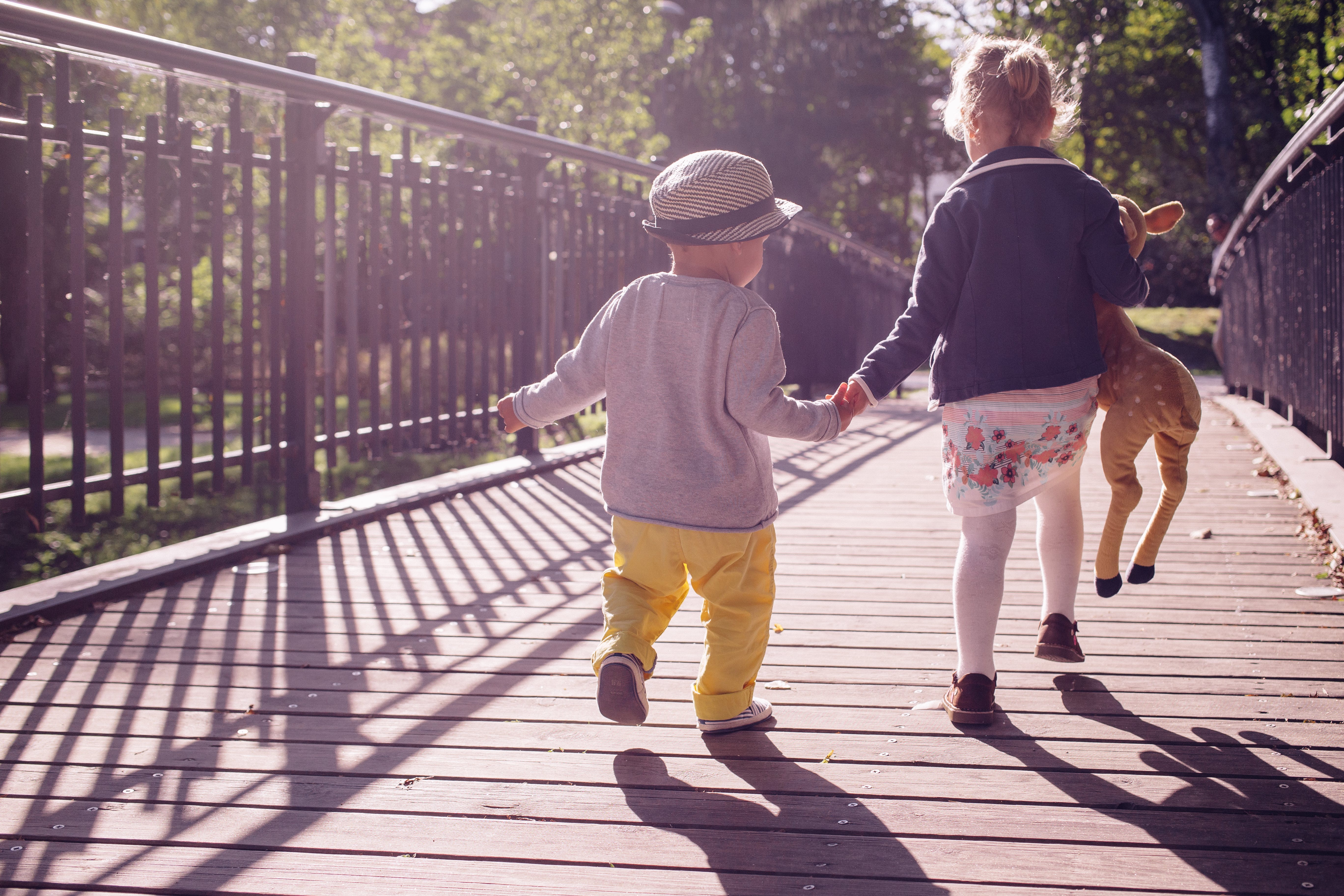 Boy and Girl Walking on Bridge during Daytime