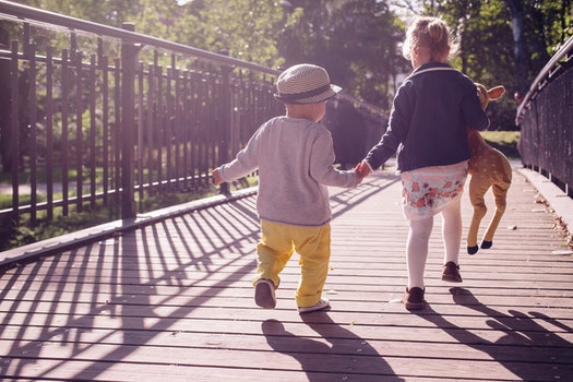 Boy and Girl Walking on Bridge during Daytime