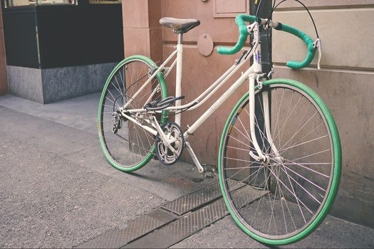 White and Green Bike Leaning on Wall